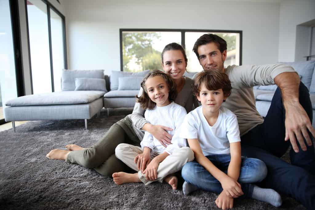 family of 4 sitting on carpet.