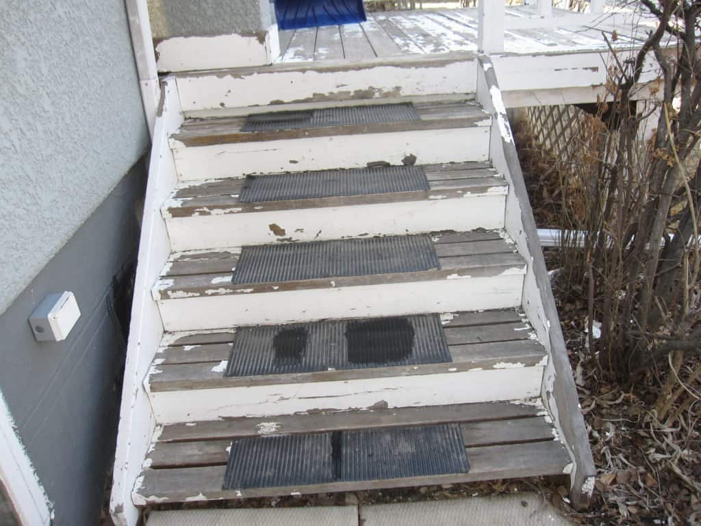 Picture of distressed, weather beaten deck stairs before the paint job.