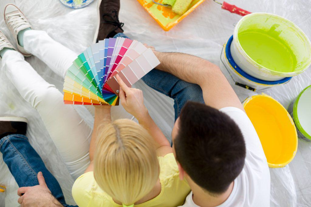 Couple sitting on floor and choosing color for painting, top view